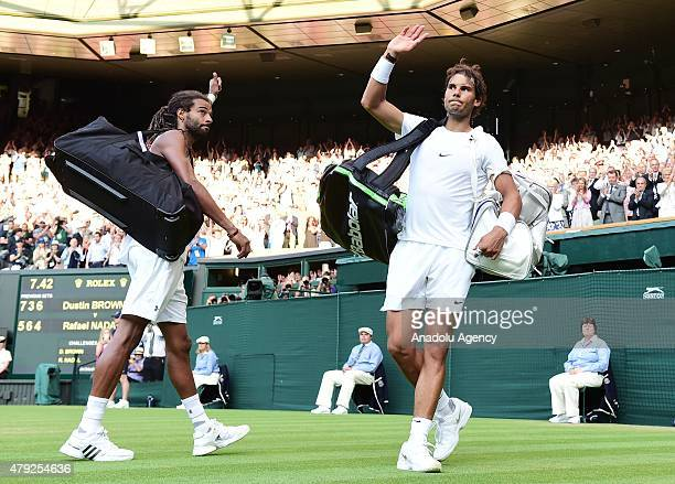 Dustin Brown of Germany and Rafael Nadal of Spain leave the pitch after their match during day four of the Wimbledon Lawn Tennis Championships at the...