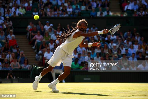 Dustin Brown of Germany stretches as he plays a backhand during the Gentlemen's Singles second round match against Andy Murray of Great Britain on...