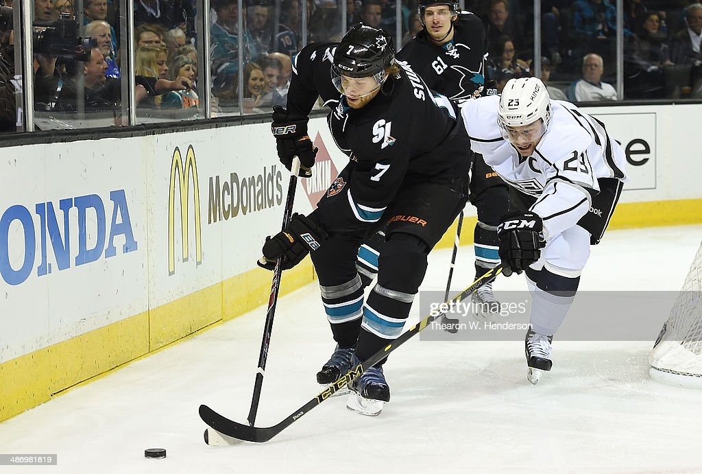 Dustin Brown #23 of the Los Angeles King skates for control of the puck with Brad Stuart #7 of the San Jose Sharks in the first period in Game Five of the First Round of the 2014 NHL Stanley Cup Playoffs at SAP Center on April 26, 2014 in San Jose, California. The Kings won the game 3-0.