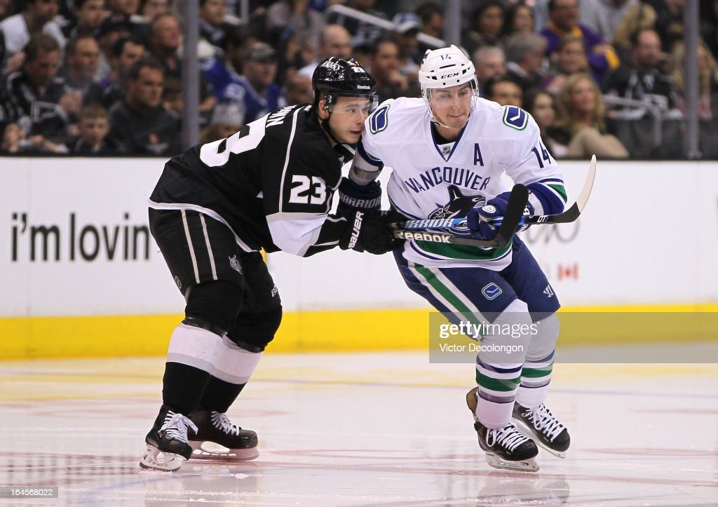 Dustin Brown #23 of the Los Angeles Kings and Alex Burrows #14 to the Vancouver Canucks vie for position during the NHL game at Staples Center on March 23, 2013 in Los Angeles, California. The Canucks defeated the Kings 1-0.