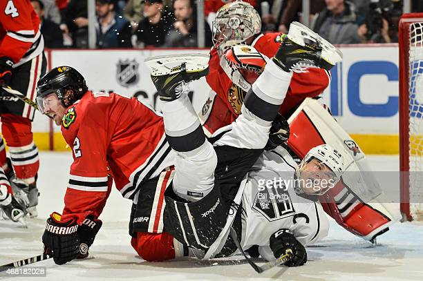 Dustin Brown of the Los Angeles Kings and Duncan Keith of the Chicago Blackhawks crash into goalie Scott Darling during the NHL game at the United...