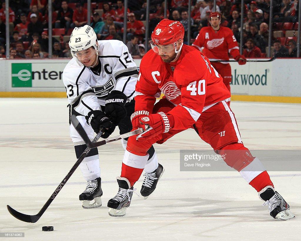 Dustin Brown #23 of the Los Angeles Kings and Henrik Zetterberg #40 of the Detroit Red Wings fight for the puck during a NHL game at Joe Louis Arena on February 10, 2013 in Detroit, Michigan.
