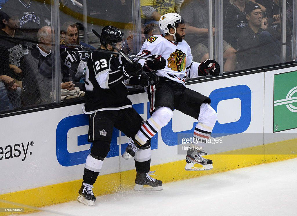 Dustin Brown #23 of the Los Angeles Kings and Johnny Oduya #27 of the Chicago Blackhawks collide near the end boards in the third period of Game Four of the Western Conference Final during the 2013 NHL Stanley Cup Playoffs at Staples Center on June 6, 2013 in Los Angeles, California. The Blackhawks defeated the Kings 3-2.