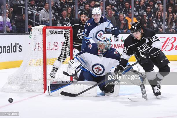 Dustin Brown of the Los Angeles Kings battles for the puck against Steve Mason of the Winnipeg Jets at STAPLES Center on November 22 2017 in Los...