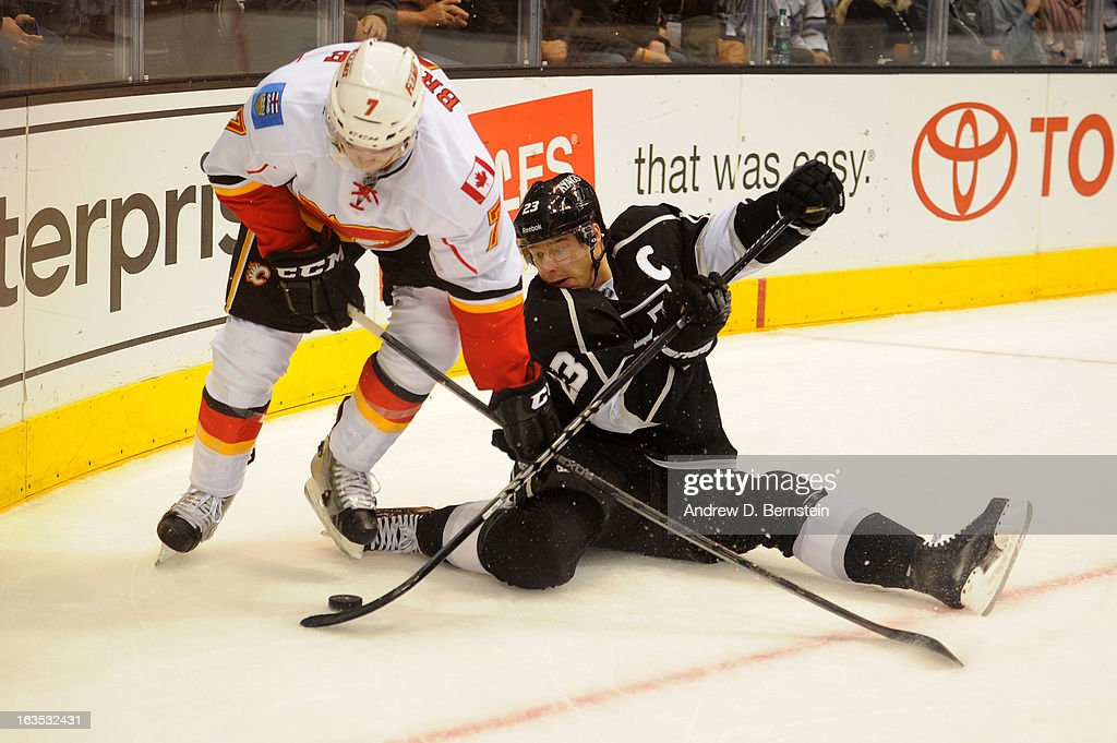 Dustin Brown #23 of the Los Angeles Kings battles for the puck against TJ Brodie #7 of the Calgary Flames at Staples Center on March 11, 2013 in Los Angeles, California.