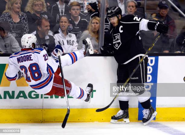 Dustin Brown of the Los Angeles Kings checks Dominic Moore of the New York Rangers in the second period during Game Five of the 2014 Stanley Cup...