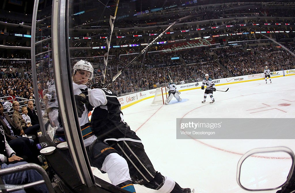 Dustin Brown #23 of the Los Angeles Kings checks Justin Braun #61 of the San Jose Sharks into the corner glass in the second period during the NHL game at Staples Center on March 16, 2013 in Los Angeles, California. The Kings defeated the Sharks 5-2.