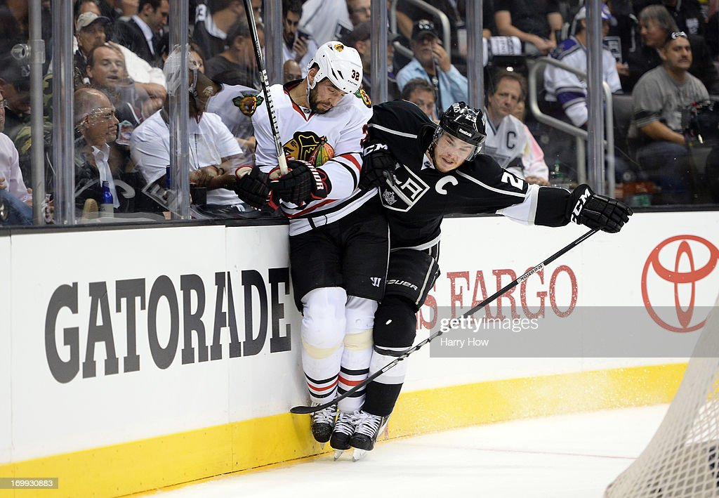 Dustin Brown #23 of the Los Angeles Kings checks <a gi-track='captionPersonalityLinkClicked' href=/galleries/search?phrase=Michal+Rozsival&family=editorial&specificpeople=216462 ng-click='$event.stopPropagation()'>Michal Rozsival</a> #32 of the Chicago Blackhawks at the end boards in the third period of Game Three of the Western Conference Final during the 2013 NHL Stanley Cup Playoffs at Staples Center on June 4, 2013 in Los Angeles, California. The Kings defeated the Blackhawks 3-1.