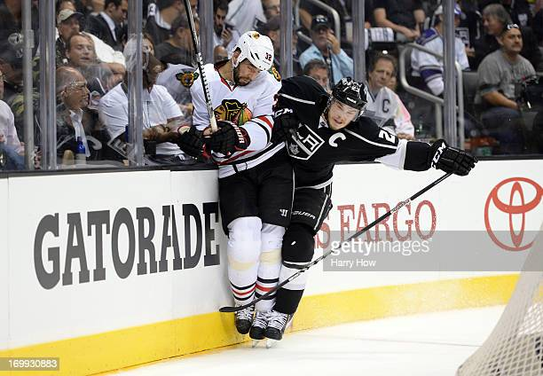 Dustin Brown of the Los Angeles Kings checks Michal Rozsival of the Chicago Blackhawks at the end boards in the third period of Game Three of the...