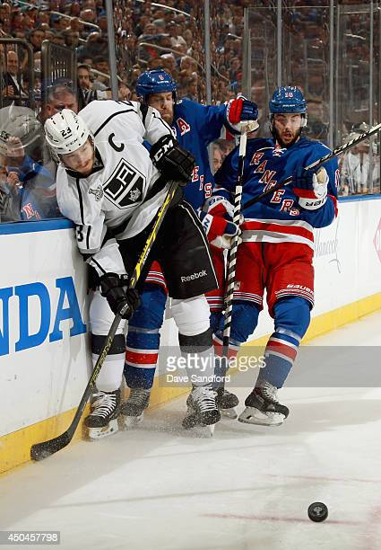 Dustin Brown of the Los Angeles Kings Dan Girardi and Derick Brassard of the New York Rangers battle for the puck during the first period of Game...