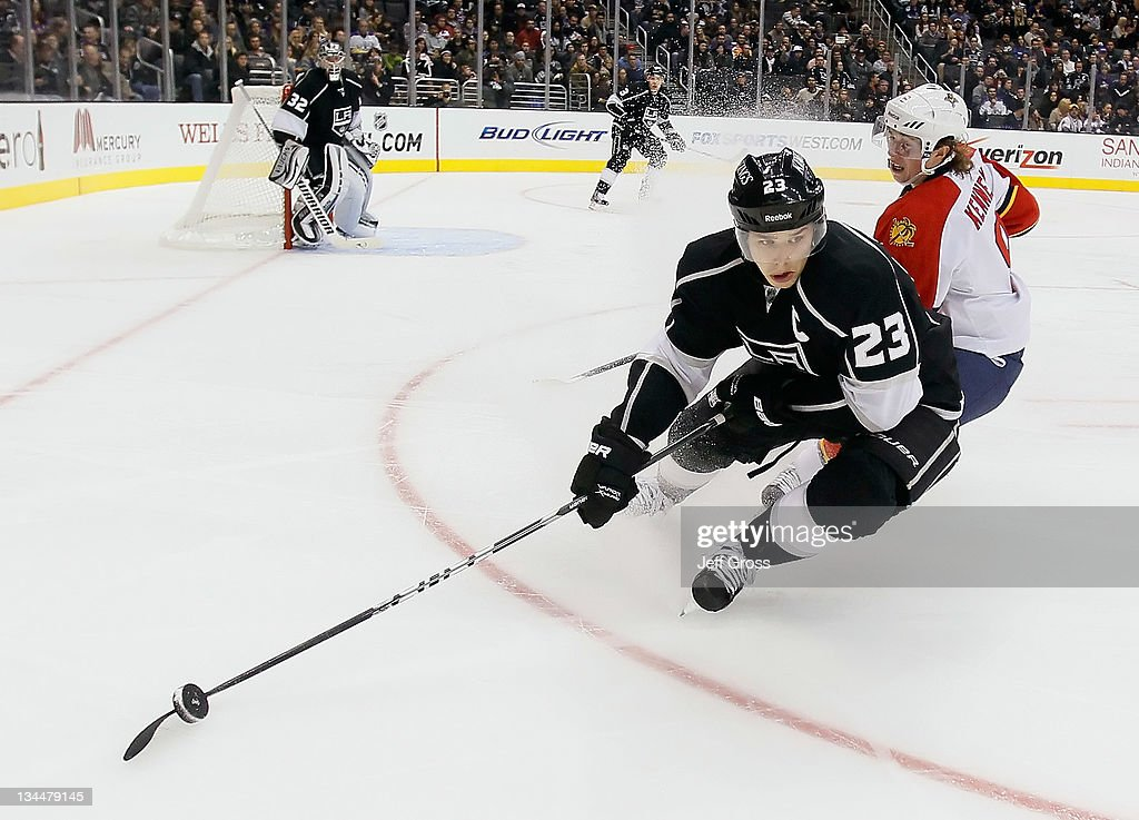 Dustin Brown #23 of the Los Angeles Kings eludes a check by Tim Kennedy #8 of the Florida Panthers in the third period at Staples Center on December 1, 2011 in Los Angeles, California. The Kings defeated the Panthers 2-1.