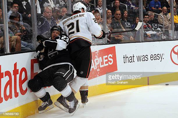 Dustin Brown of the Los Angeles Kings gets checked by Sheldon Brookbank of the Anaheim Ducks during a preseason game at Staples Center on September...