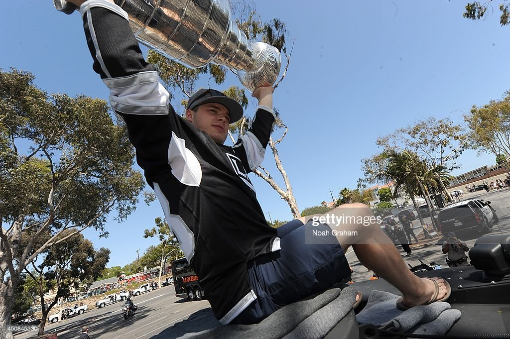 Dustin Brown #23 of the Los Angeles Kings hoists the Stanley Cup up in the air during the Los Angeles Kings South Bay Victory Parade on June 18, 2014 in Redondo Beach, California.