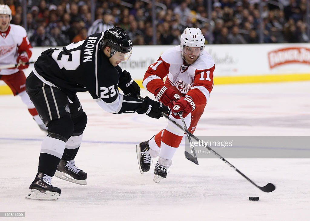Dustin Brown #23 of the Los Angeles Kings is pursued by <a gi-track='captionPersonalityLinkClicked' href=/galleries/search?phrase=Daniel+Cleary&family=editorial&specificpeople=220490 ng-click='$event.stopPropagation()'>Daniel Cleary</a> #11 of the Detroit Red Wings for the puck in the third period at Staples Center on February 27, 2013 in Los Angeles, California. The Kings defeated the Red Wings 2-1.