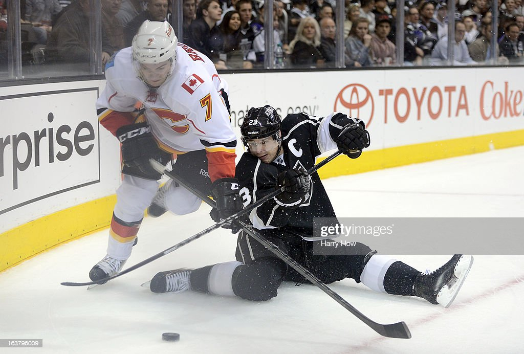 Dustin Brown #23 of the Los Angeles Kings makes a pass from the ice in front of T.J. Brodie #7 of the Calgary Flames during the second period at Staples Center on March 11, 2013 in Los Angeles, California.