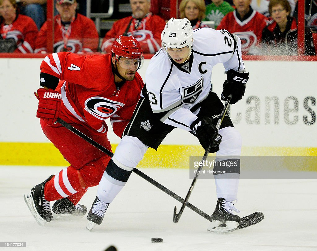 Dustin Brown #23 of the Los Angeles Kings moves the puck against <a gi-track='captionPersonalityLinkClicked' href=/galleries/search?phrase=Andrej+Sekera&family=editorial&specificpeople=722503 ng-click='$event.stopPropagation()'>Andrej Sekera</a> #4 of the Carolina Hurricanes during play at PNC Arena on October 11, 2013 in Raleigh, North Carolina.