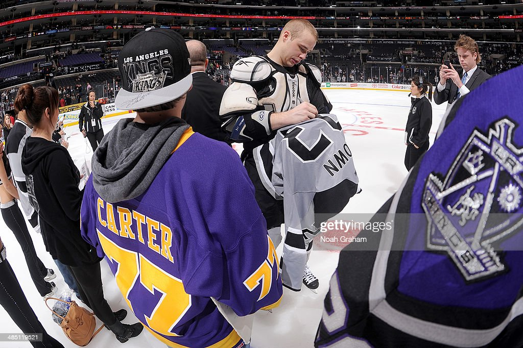 Dustin Brown #23 of the Los Angeles Kings signs his jersey for a fan after the game against the Anaheim Ducks at Staples Center on April 12, 2014 in Los Angeles, California.