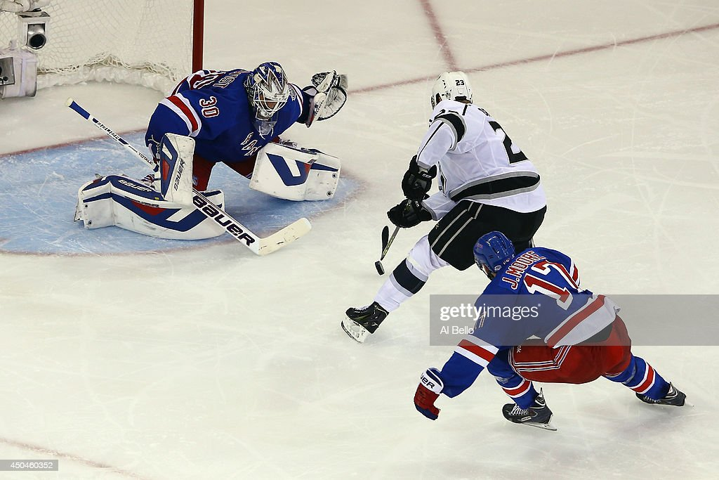 Dustin Brown #23 of the Los Angeles Kings skates in on Henrik Lundqvist #30 of the New York Rangers with John Moore #17 of the New York Rangers defending during the second period of Game Four of the 2014 NHL Stanley Cup Final at Madison Square Garden on June 11, 2014 in New York, New York.