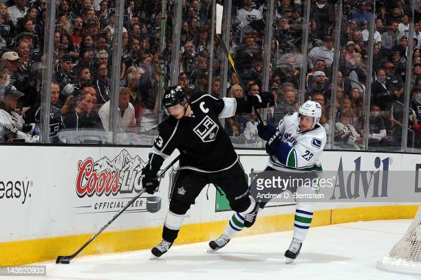 Dustin Brown of the Los Angeles Kings skates with the puck against Alexander Edler of the Vancouver Canucks in Game Four of the Western Conference...