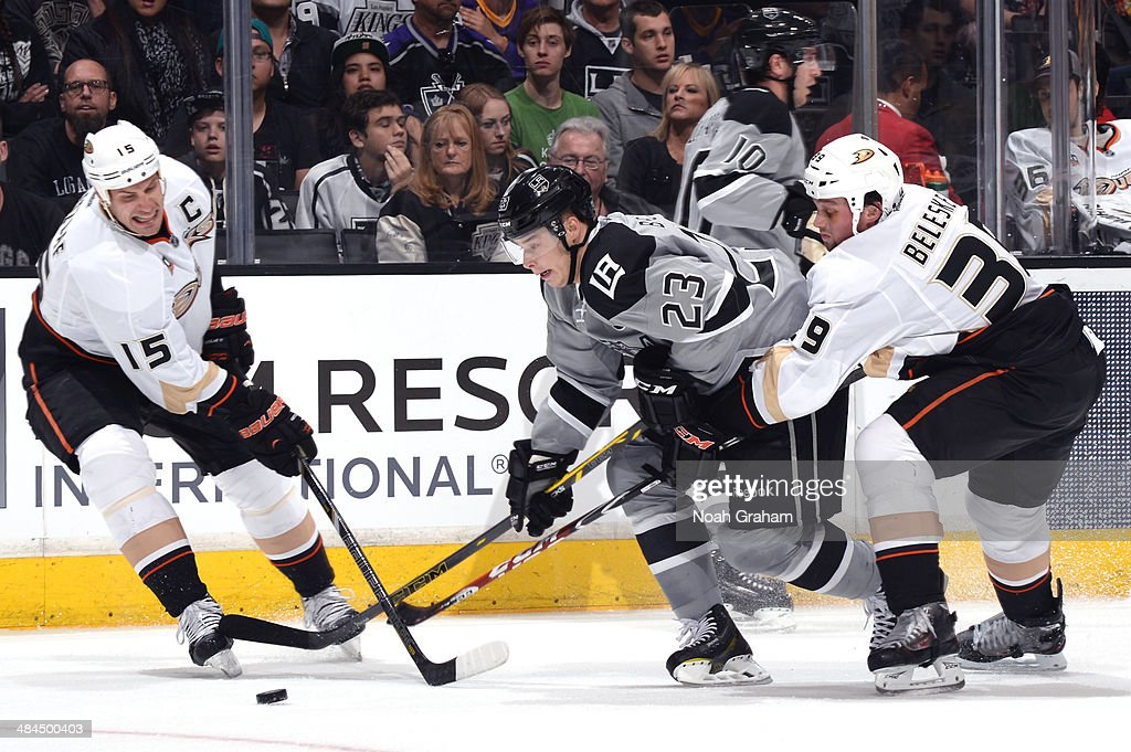 Dustin Brown #23 of the Los Angeles Kings skates with the puck against Ryan Getzlaf #15 and Matt Beleskey #39 of the Anaheim Ducks at Staples Center on April 12, 2014 in Los Angeles, California.