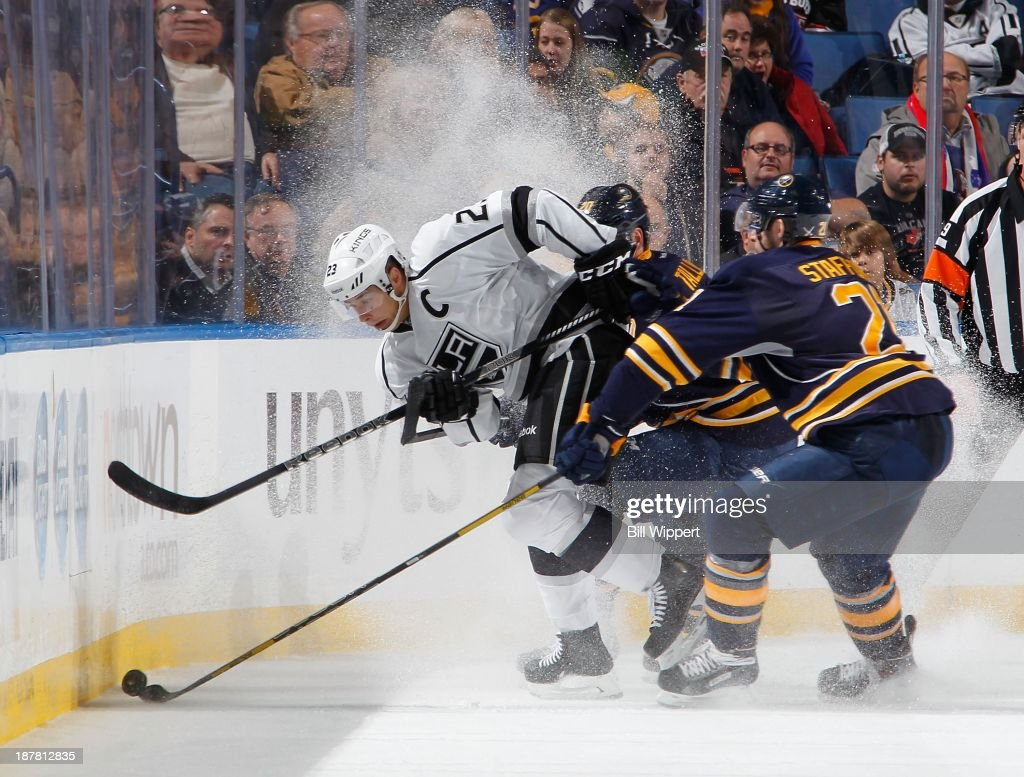 Dustin Brown #23 of the Los Angeles Kings stops to control the puck against Henrik Tallinder #20 and Drew Stafford #21 of the Buffalo Sabres on November 12, 2013 at the First Niagara Center in Buffalo, New York. Buffalo won, 3-2.