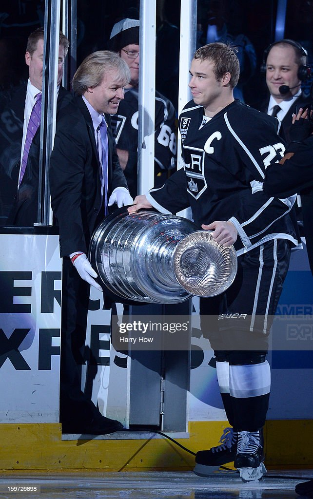 Dustin Brown #23 of the Los Angeles Kings takes the Stanley Cup from Phil Pritchard of the Hockey Hall of Fame before the NHL season opening game between the Chicago Blackhawks and the Los Angeles Kings at Staples Center on January 19, 2013 in Los Angeles, California.