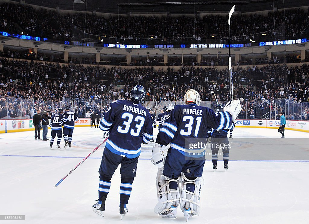 <a gi-track='captionPersonalityLinkClicked' href=/galleries/search?phrase=Dustin+Byfuglien&family=editorial&specificpeople=672505 ng-click='$event.stopPropagation()'>Dustin Byfuglien</a> #33 and Ondrej Pavelec #31 of the Winnipeg Jets salute the fans following a thrilling 5-4 come-from-behind shootout victory over the San Jose Sharks at the MTS Centre on November 10, 2013 in Winnipeg, Manitoba, Canada.