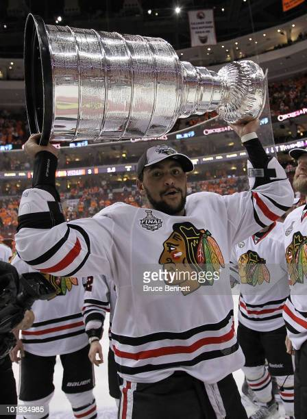 Dustin Byfuglien of the Chicago Blackhawks hoists the Stanley Cup after teammate Patrick Kane scored the gamewinning goal in overtime to defeat the...