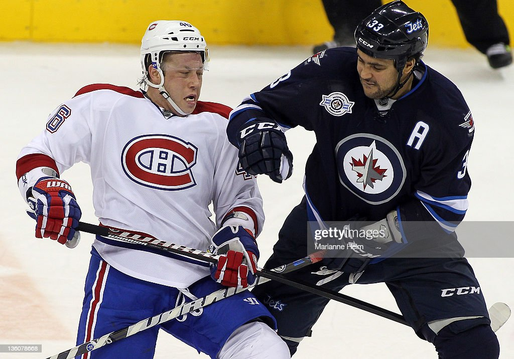 <a gi-track='captionPersonalityLinkClicked' href=/galleries/search?phrase=Dustin+Byfuglien&family=editorial&specificpeople=672505 ng-click='$event.stopPropagation()'>Dustin Byfuglien</a> #33 of the Winnipeg Jets and <a gi-track='captionPersonalityLinkClicked' href=/galleries/search?phrase=Andrei+Kostitsyn&family=editorial&specificpeople=668411 ng-click='$event.stopPropagation()'>Andrei Kostitsyn</a> #46 of the Montreal Canadiens collide in NHL action at the MTS Centre on December 22, 2011 in Winnipeg, Manitoba, Canada.