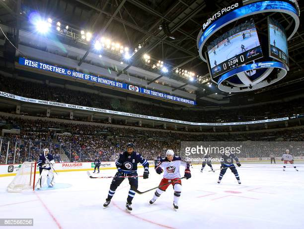 Dustin Byfuglien of the Winnipeg Jets and Cam Atkinson of the Columbus Blue Jackets keep an eye on the play along the boards during first period...
