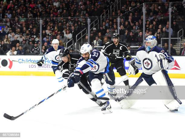 Dustin Byfuglien of the Winnipeg Jets and Dustin Brown of the Los Angeles Kings reach for a rebound in front of Connor Hellebuyck of the Winnipeg...
