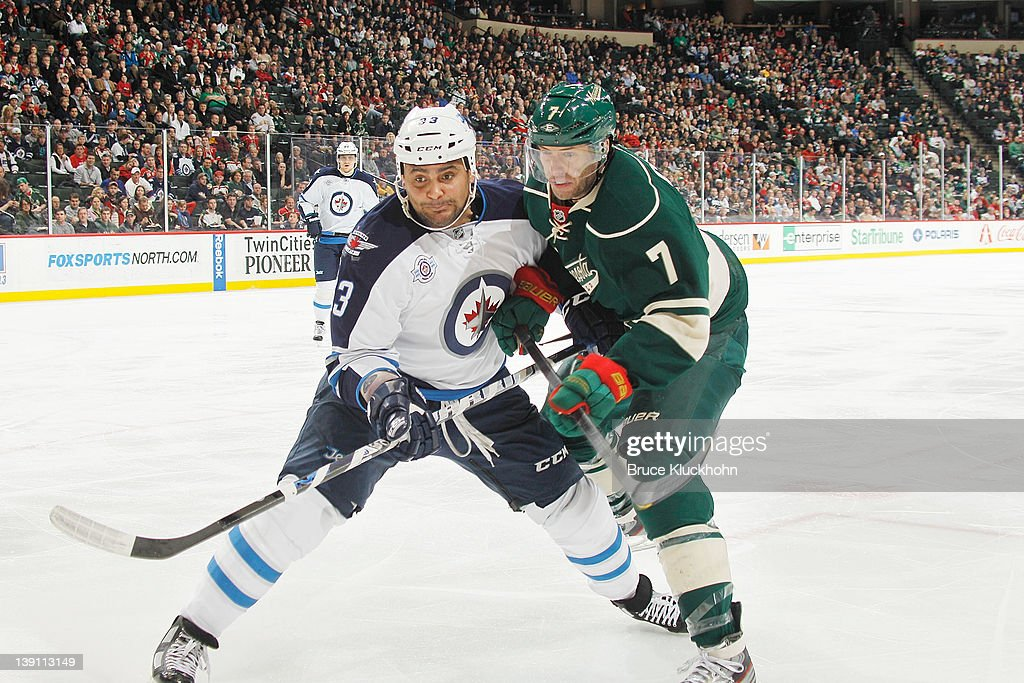 <a gi-track='captionPersonalityLinkClicked' href=/galleries/search?phrase=Dustin+Byfuglien&family=editorial&specificpeople=672505 ng-click='$event.stopPropagation()'>Dustin Byfuglien</a> #33 of the Winnipeg Jets and <a gi-track='captionPersonalityLinkClicked' href=/galleries/search?phrase=Matt+Cullen&family=editorial&specificpeople=536122 ng-click='$event.stopPropagation()'>Matt Cullen</a> #7 of the Minnesota Wild skate to the puck during the game at the Xcel Energy Center on February 16, 2012 in St. Paul, Minnesota.