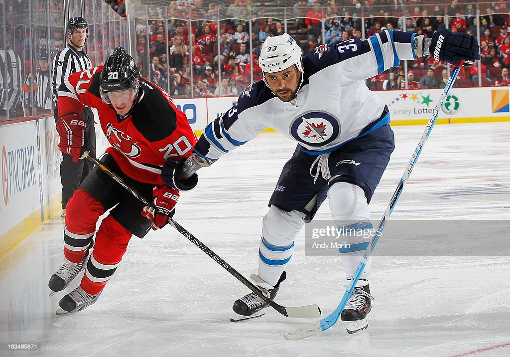 Dustin Byfuglien #33 of the Winnipeg Jets and Ryan Carter #20 of the New Jersey Devils battle for position during the game at the Prudential Center on March 10, 2013 in Newark, New Jersey.