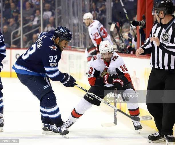 Dustin Byfuglien of the Winnipeg Jets and Tom Pyatt of the Ottawa Senators fight for the loose puck during third period action at the Bell MTS Place...