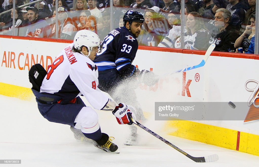 Dustin Byfuglien #33 of the Winnipeg Jets backhands the puck along the boards away from Alex Ovechkin #8 of the Washington Capitals during second period action at the MTS Centre on March 2, 2013 in Winnipeg, Manitoba, Canada.