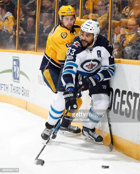 Dustin Byfuglien of the Winnipeg Jets battles along the boards against Filip Forsberg of the Nashville Predators during an NHL game at Bridgestone...