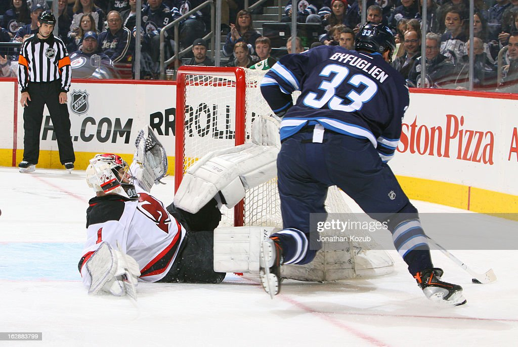 Dustin Byfuglien #33 of the Winnipeg Jets carries the puck around the net as goaltender Johan Hedberg #1 of the New Jersey Devils falls in the crease during third period action at the MTS Centre on February 28, 2013 in Winnipeg, Manitoba, Canada.