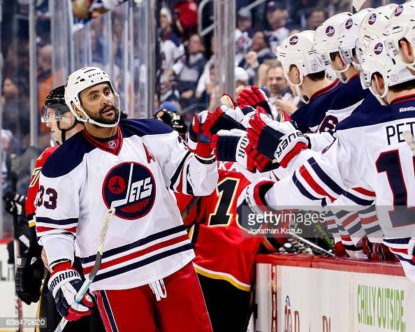 Dustin Byfuglien of the Winnipeg Jets celebrates a first period goal against the Calgary Flames with teammates at the bench at the MTS Centre on...