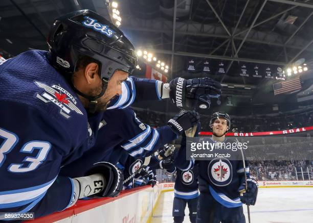 Dustin Byfuglien of the Winnipeg Jets celebrates a second period goal against the Ottawa Senators with teammate Nikolaj Ehlers at the bench at the...