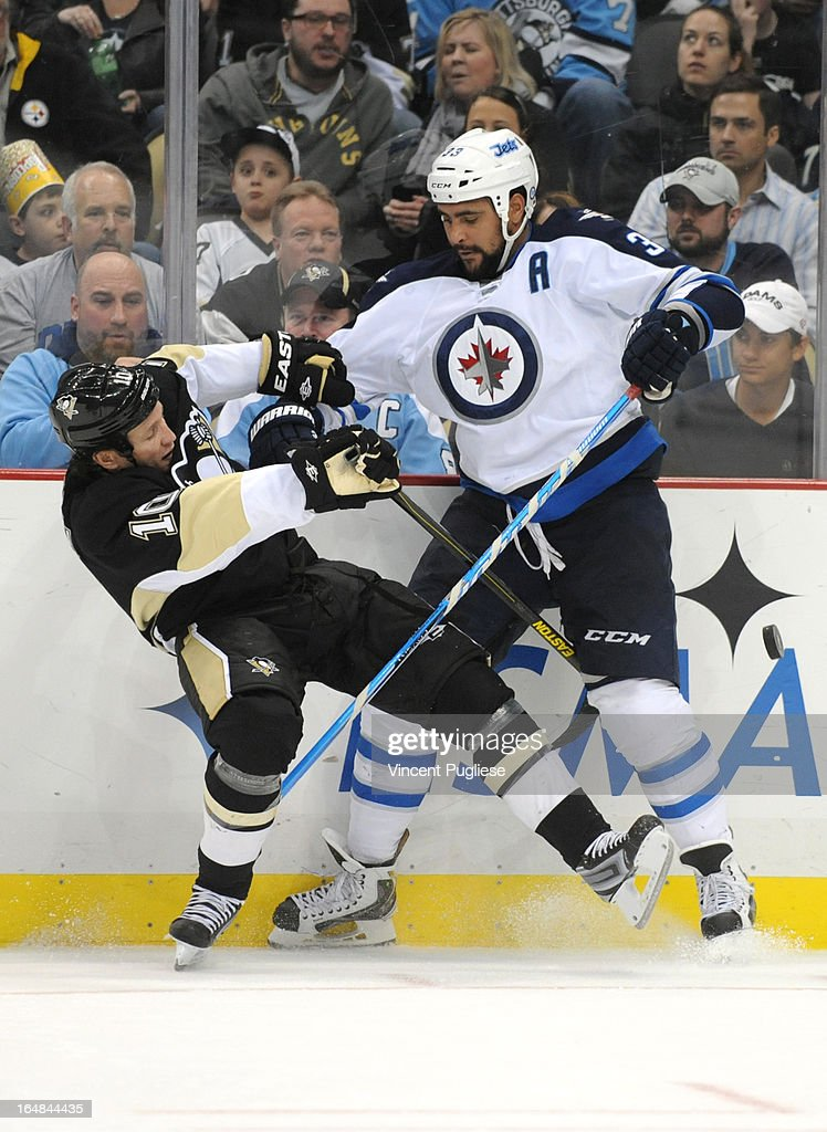 Dustin Byfuglien #33 of the Winnipeg Jets checks Brenden Morrow #10 of the Pittsburgh Penguins in the third period on February 28, 2013 at the CONSOL Energy Center in Pittsburgh, Pennsylvania.