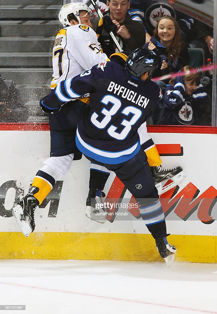 <a gi-track='captionPersonalityLinkClicked' href=/galleries/search?phrase=Dustin+Byfuglien&family=editorial&specificpeople=672505 ng-click='$event.stopPropagation()'>Dustin Byfuglien</a> #33 of the Winnipeg Jets checks <a gi-track='captionPersonalityLinkClicked' href=/galleries/search?phrase=Gabriel+Bourque&family=editorial&specificpeople=5627917 ng-click='$event.stopPropagation()'>Gabriel Bourque</a> #57 of the Nashville Predators into the boards during second period action at the MTS Centre on November 8, 2013 in Winnipeg, Manitoba, Canada.