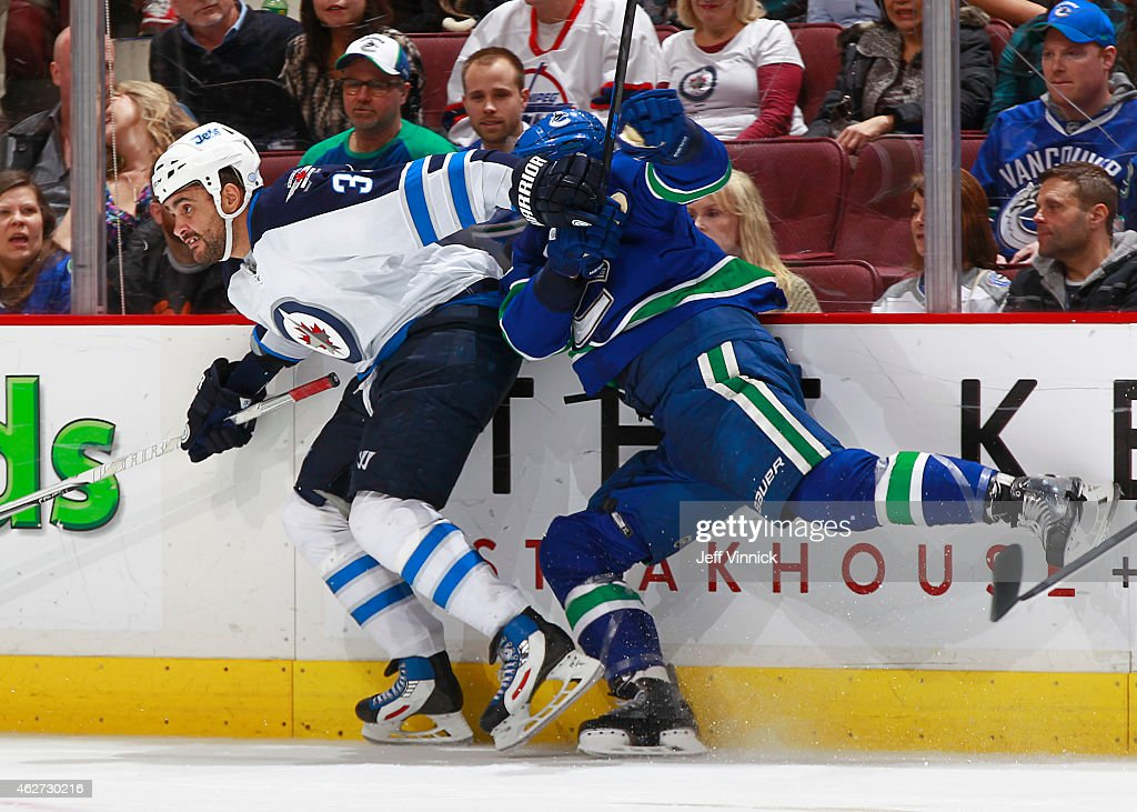 <a gi-track='captionPersonalityLinkClicked' href=/galleries/search?phrase=Dustin+Byfuglien&family=editorial&specificpeople=672505 ng-click='$event.stopPropagation()'>Dustin Byfuglien</a> #33 of the Winnipeg Jets checks <a gi-track='captionPersonalityLinkClicked' href=/galleries/search?phrase=Luca+Sbisa&family=editorial&specificpeople=4893043 ng-click='$event.stopPropagation()'>Luca Sbisa</a> #5 of the Vancouver Canucks during their NHL game at Rogers Arena February 3, 2015 in Vancouver, British Columbia, Canada. Vancouver won 3-2.