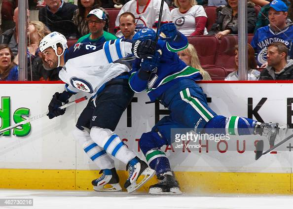Dustin Byfuglien of the Winnipeg Jets checks Luca Sbisa of the Vancouver Canucks during their NHL game at Rogers Arena February 3 2015 in Vancouver...