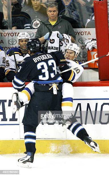 Dustin Byfuglien of the Winnipeg Jets checks Scottie Upshall of the St Louis Blues into the bench during third period action at the MTS Centre on...