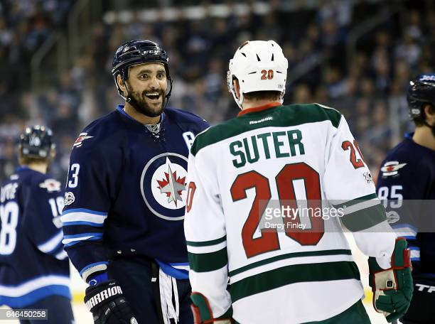Dustin Byfuglien of the Winnipeg Jets exchanges words with Ryan Suter of the Minnesota Wild during a first period stoppage in play at the MTS Centre...