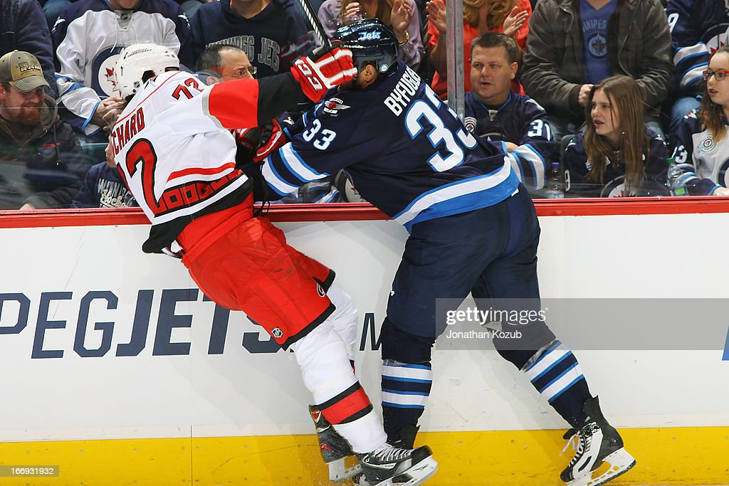 Dustin Byfuglien #33 of the Winnipeg Jets flattens Nicolas Blanchard #72 of the Carolina Hurricanes along the boards during second period action at the MTS Centre on April 18, 2013 in Winnipeg, Manitoba, Canada.