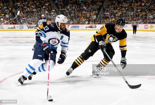 Dustin Byfuglien of the Winnipeg Jets handles the puck against Brian Dumoulin of the Pittsburgh Penguins at PPG Paints Arena on October 26 2017 in...