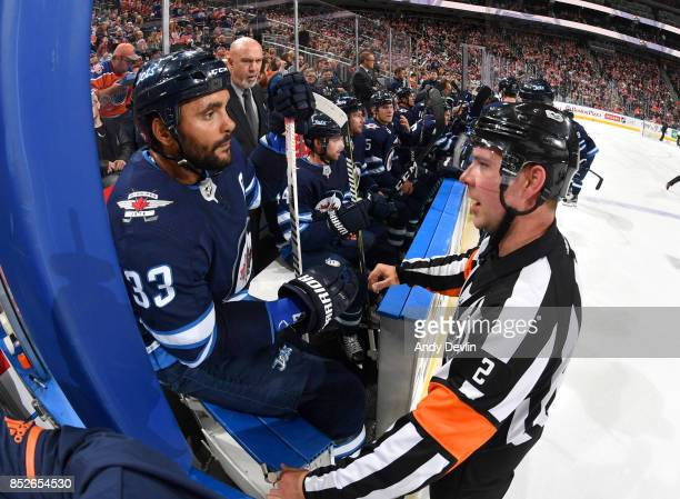 Dustin Byfuglien of the Winnipeg Jets has a discussion with Mike Hasenfratz during the preseason game against the Edmonton Oilers on September 23...