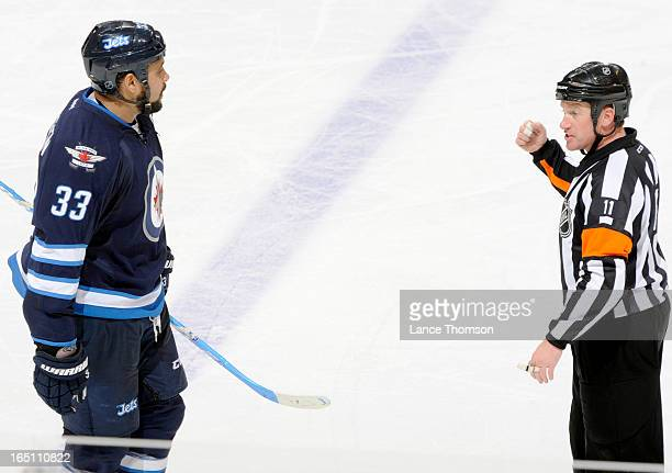 Dustin Byfuglien of the Winnipeg Jets has words with referee Kelly Sutherland during a second period stoppage against the Carolina Hurricanes at the...