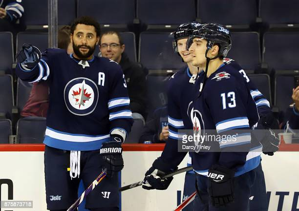 Dustin Byfuglien of the Winnipeg Jets makes a point to teammates Jacob Trouba and Brandon Tanev during the pregame warm up prior to NHL action...